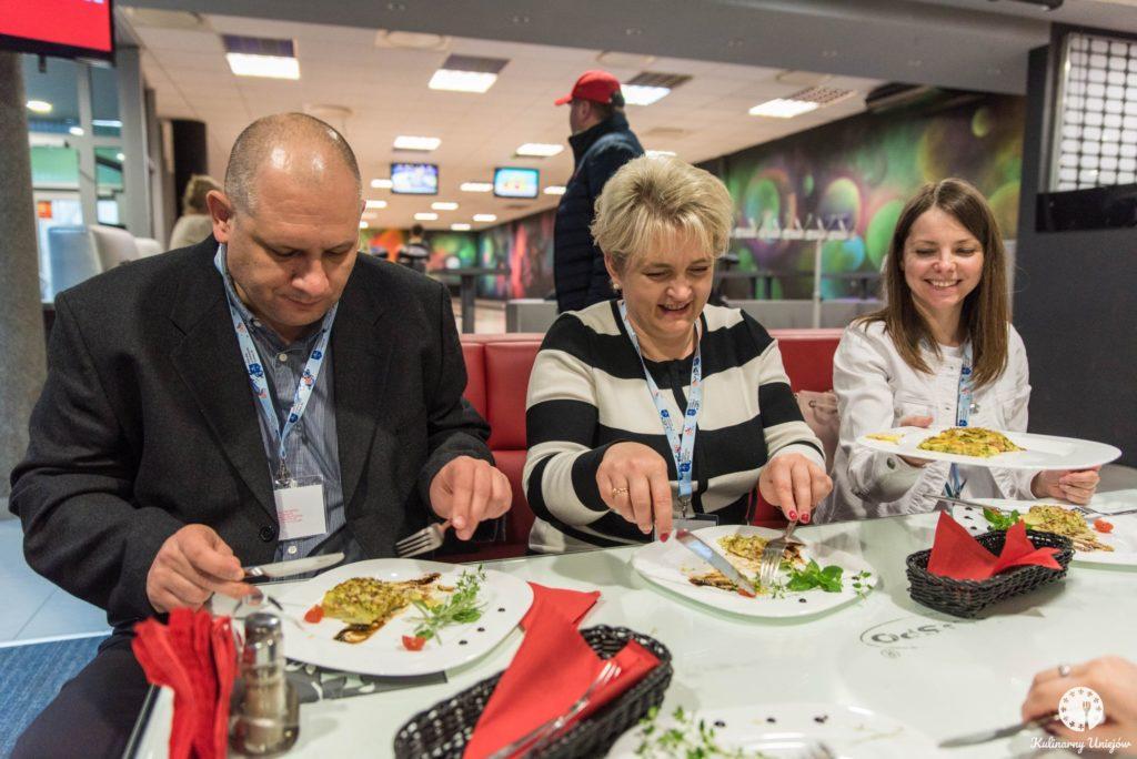 Mężczyzna i dwie kobiety siedzą przy stole i jedzą potrawy