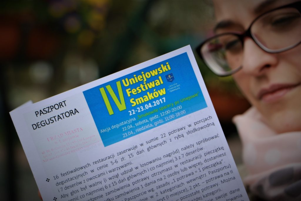 Kobieta w okularach czyta paszport degustatora