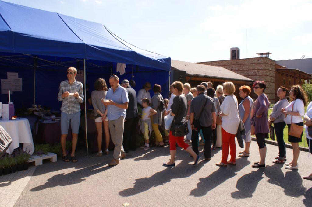 Ludzie stoją w kolejce do granatowego namiotu