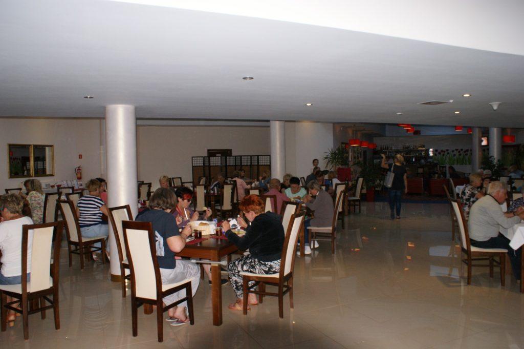 Sala restauracyjna. Przy wszystkich stolikach siedzą ludzie i jedzą
