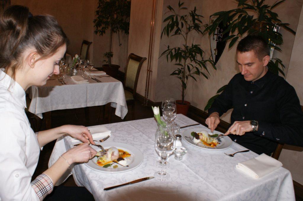 Kobieta i mężczyzna siedzą przy stole nakrytym białym obrusem i jedzą potrawy