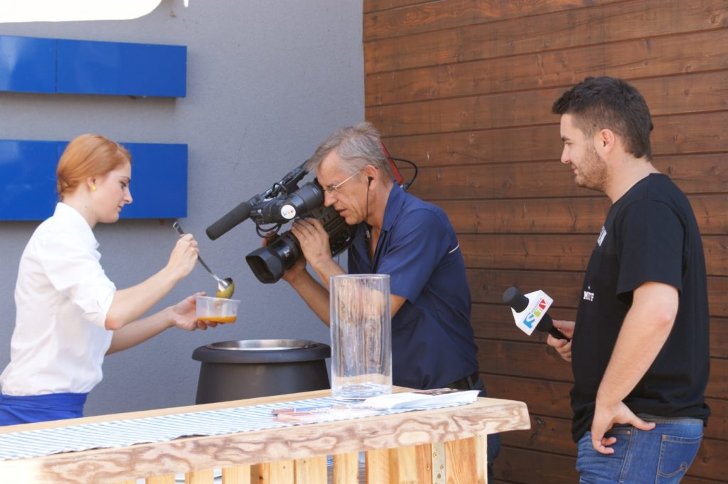 Kamerzysta filmuje kobietę w białej bluzce nalewającą zupę do plastikowego pojemnika
