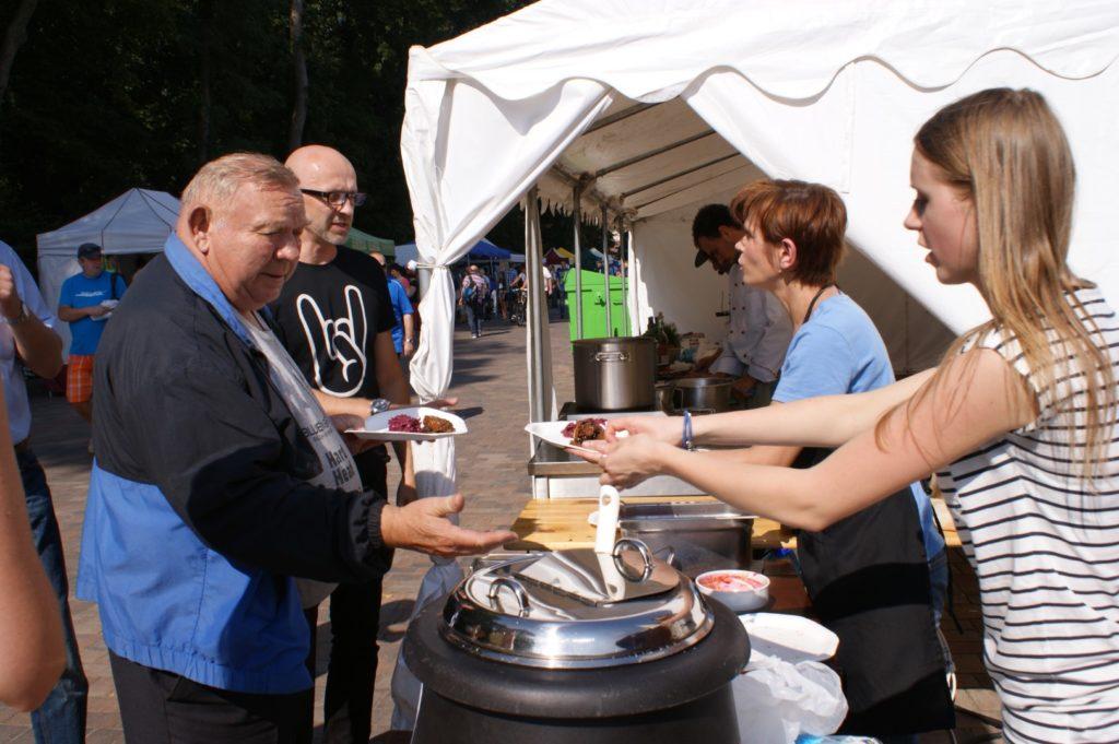 Ludzie degustują potrawy z kuchni na wolnym powietrzu