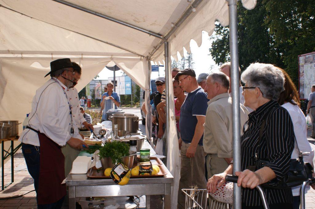 Ludzie przyglądają się kucharzom gotującym w kuchni na wolnym powietrzu