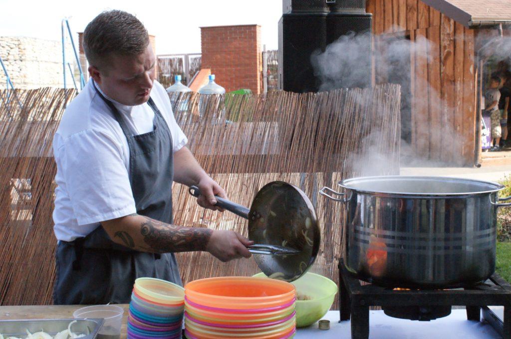 Kucharz gotuje w kuchni na wolnym powietrzu