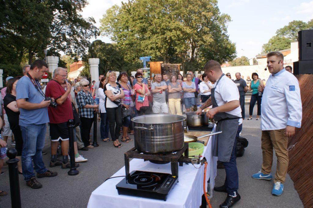 Tłum się przygląda kucharzom gotującym w kuchni na wolnym powietrzu