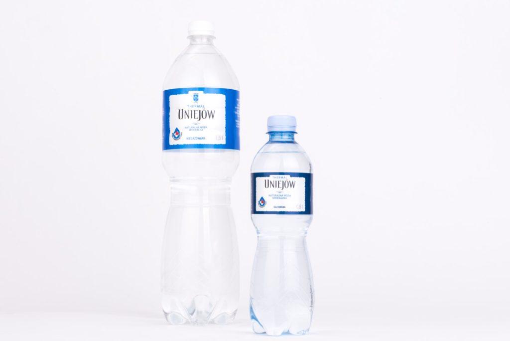 Dwie butelki z wodą - po prawej większa, po lewej mniejsza