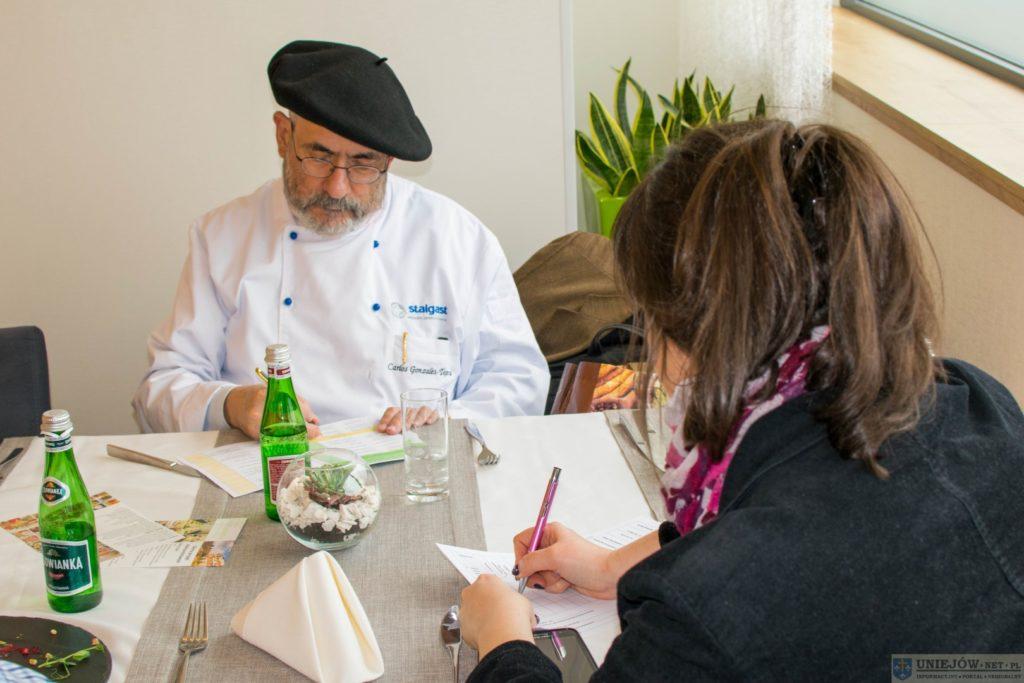 Mężczyzna z brodą w czarnym berecie na głowie pisze na kartce. Na pierwszym planie odwrócona kobieta pisząca na kartce