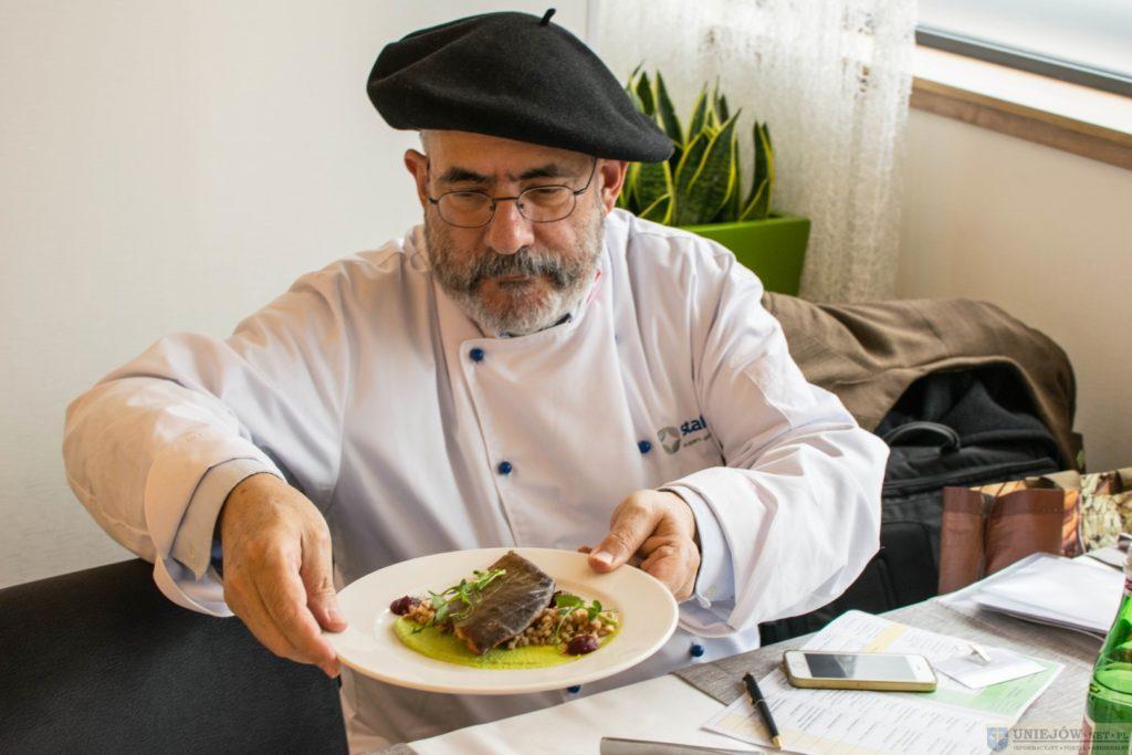 Mężczyzna z brodą w czarnym berecie na głowie trzyma potrawę na talerzu