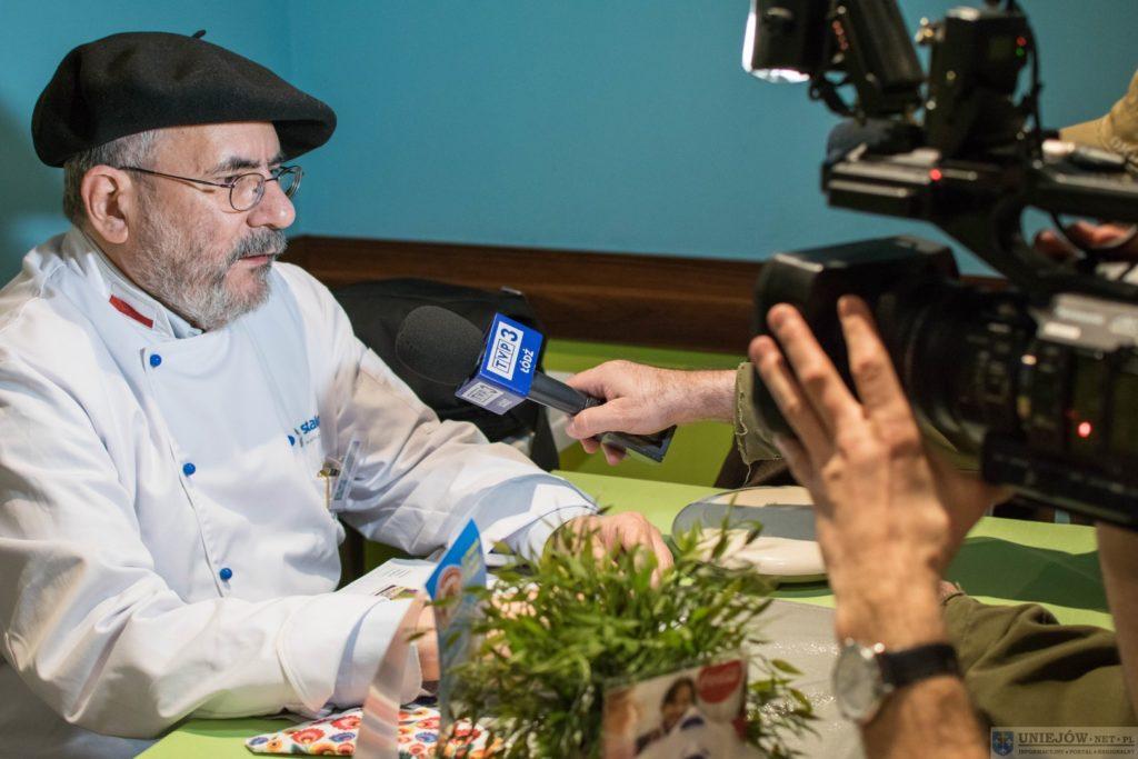 Mężczyzna z brodą w czarnym berecie na głowie mówi do mikrofonu