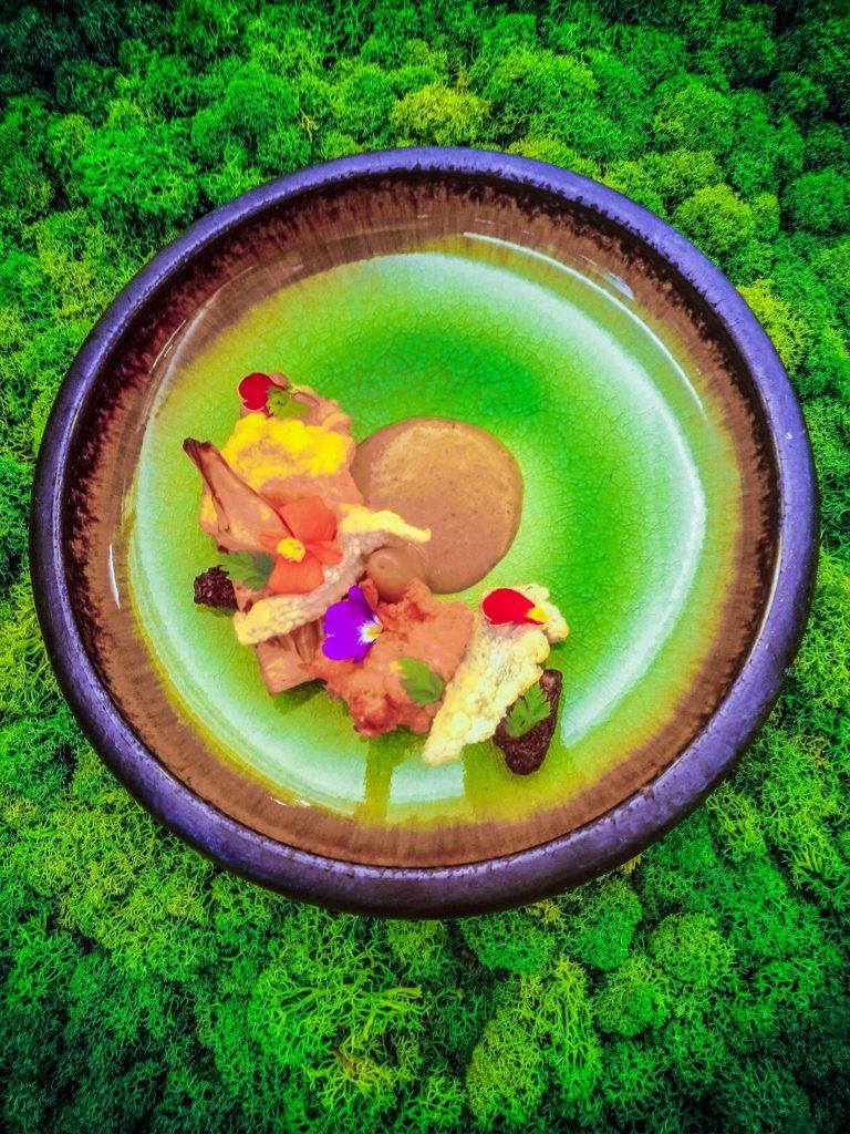 Danie składające się z różnokolorowych składników podane na zielono-fioletowym płaskim talerzu